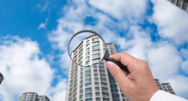 A hand holding a magnifying glass against the backdrop of an apartment